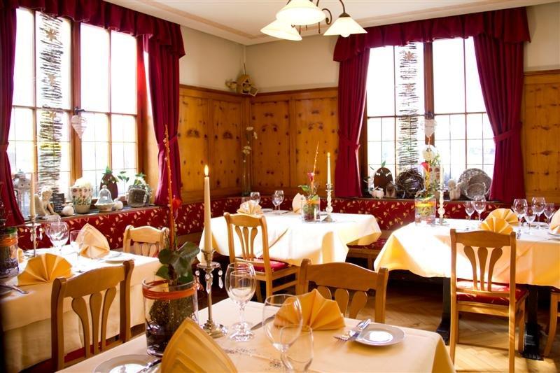 Gastraum mit Tischen, Bänke und Stühle. Auf dem Tisch stehen Teller, Besteck und Gläser