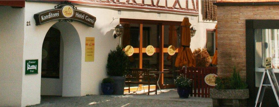 Ein Fachwerkhaus mit einem großen Bogen als Eingang. Darüber ein Schild mit der Aufschrift Konditorei Hotel Garni.