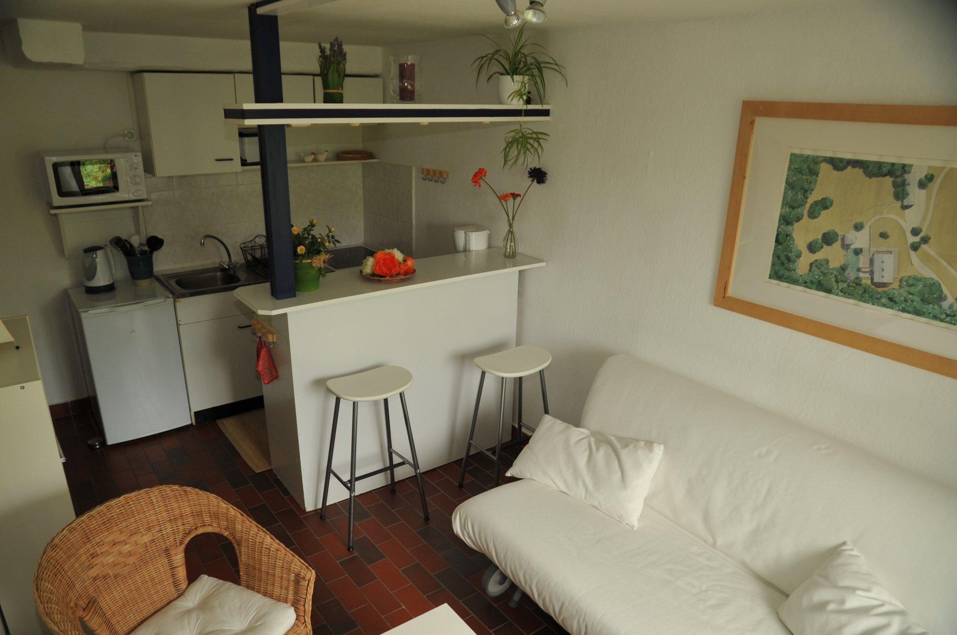 Küche und Bar mit zwei Hocker, Sofa und Sessel