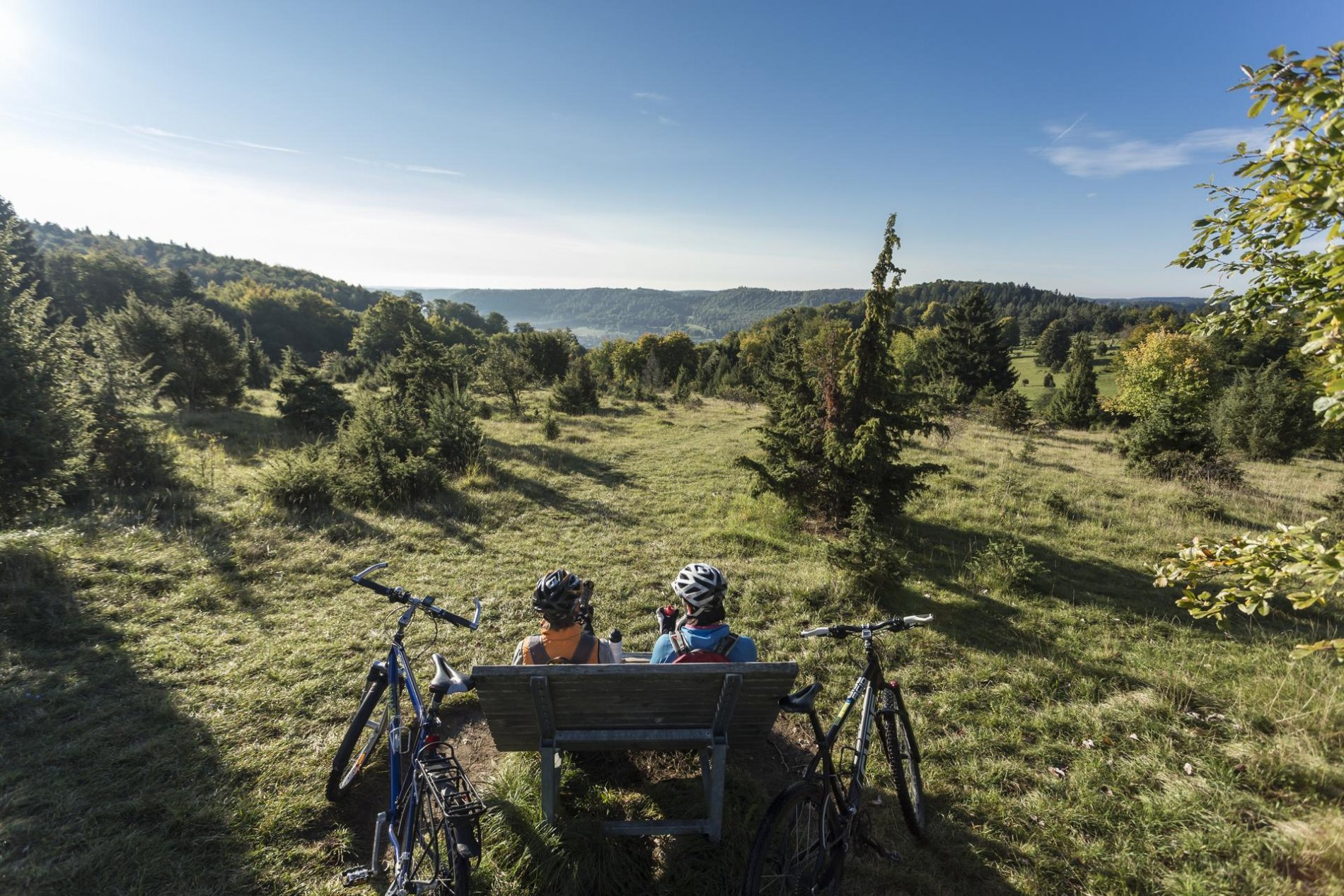 Zwei Radfahrer*innen sitzen auf einer Holzbank und genießen den Ausblick über die weite Alblandschaft mit viel Wald. Neben ihnen stehen zwei Fahrräder. Es ist sonnig, aber frisch.