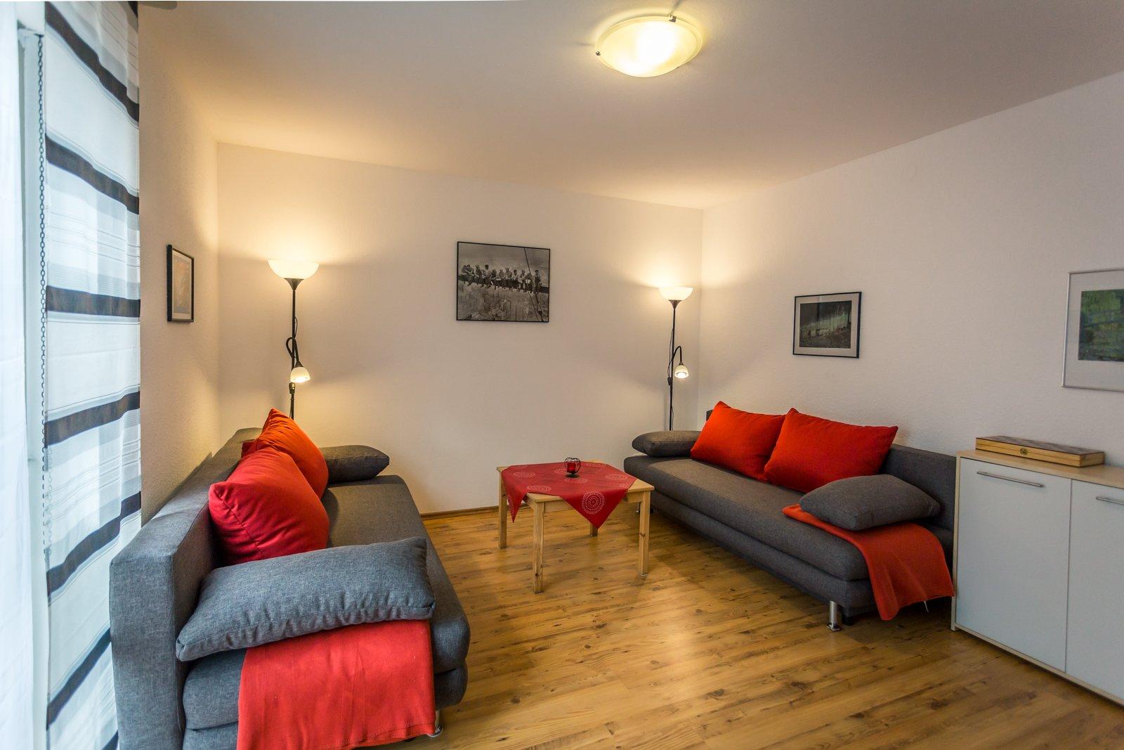 2 Sofas mit roten Kissen und Wohnzimmertisch auf Holzboden