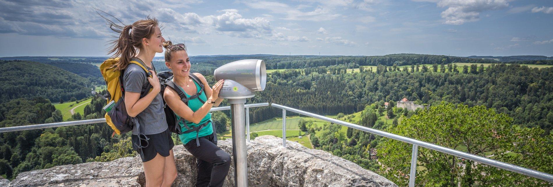Zwei Wanderer*innen stehen auf einer Aussichtplattform an einem Viscope Erlebnisfernrohr und blicken lächelnd in die Ferne und ihre Haare wehen im Wind. Hinter ihnen ist der Ausblick über die Albhochfläche und im Tal ist eine Burg.