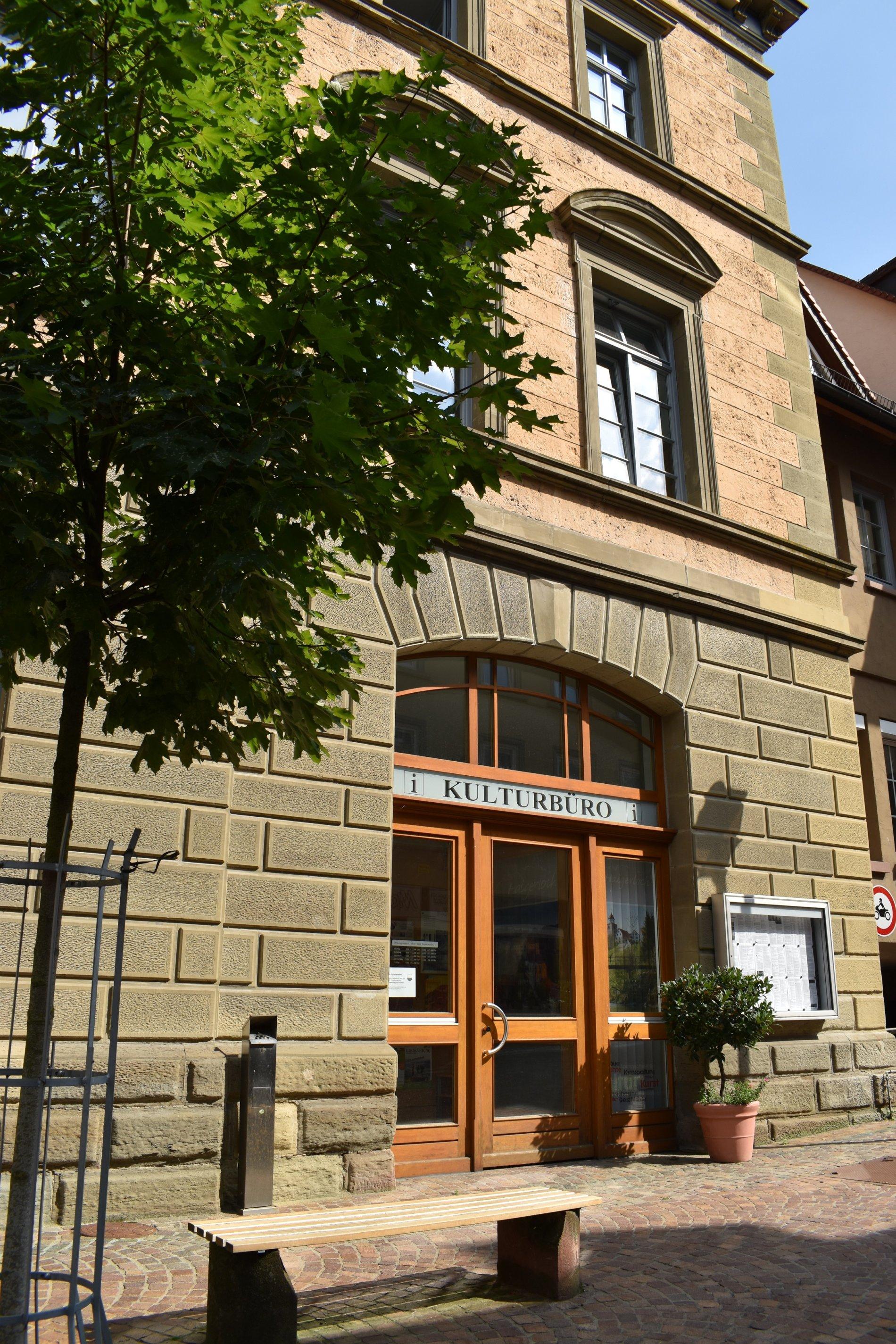 Touristinfogebäude mit Eingangstüre, Vorplatz und Ruhebank