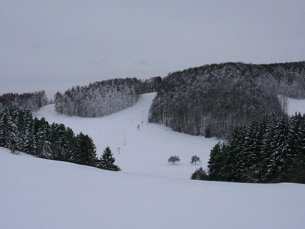 Schneebedeckt Hänge, die hinunter in ein Tal führen. In der Bildmitte ist ein Schlepplift für Wintersportler. An den Hängen sind immer wieder Waldflächen. Der Himmel ist grau.