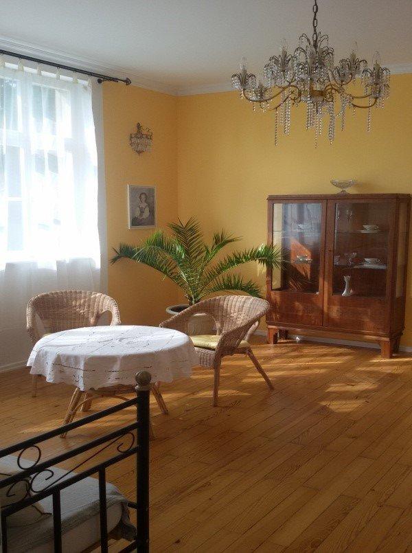 Großes Wohnzimmer mit gelben Wänden einem Kronleuchter und zwei Sitzgelegenheiten mit Tisch