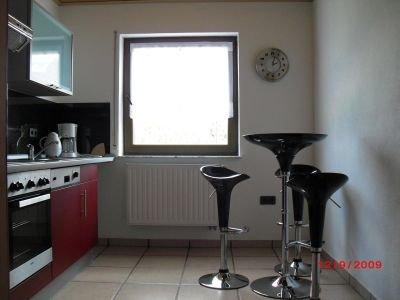 Moderne Küche mit Barhockern und einem Stehtisch