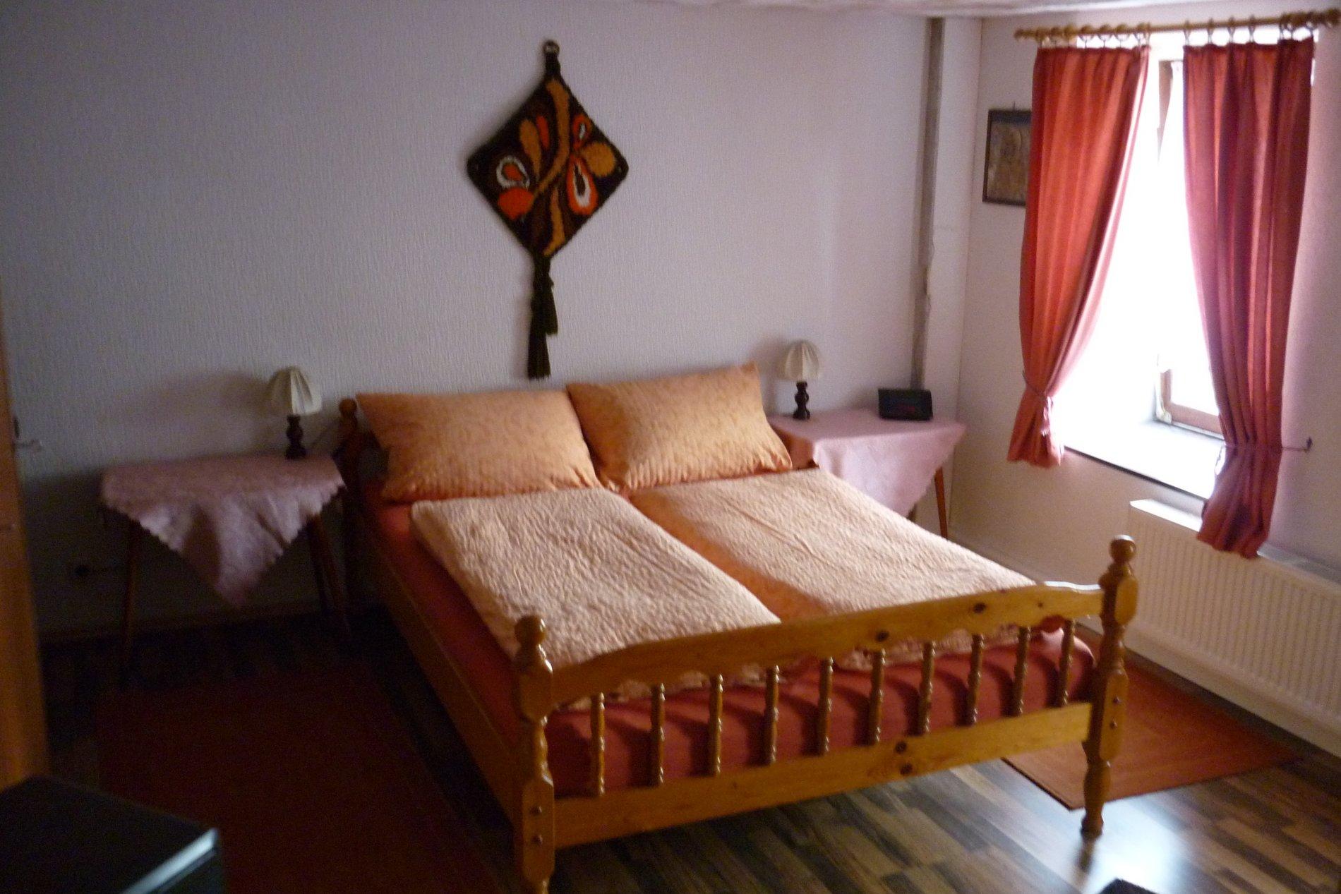 Doppelbett mit zwei Nachttischen und Laminatboden