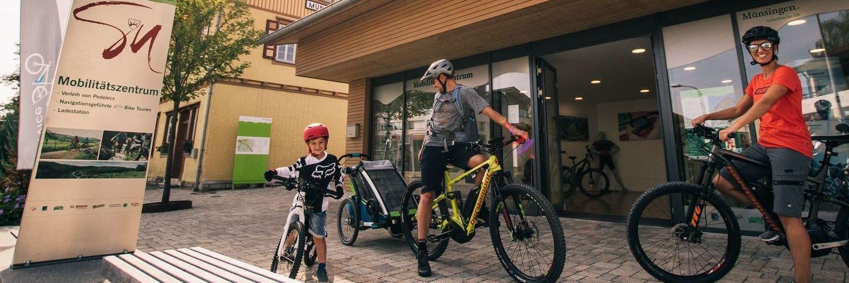 Zwei Erwachsene und ein Kind stehe in kurzer Radkleidung mit ihren Fahrrädern vor einem Gebäude. Die beiden Erwachsenen haben E-Bikes und einer einen Kinderfahrradanhänger. Vor dem Gebäude steht ein Schild mit der Aufschrift Mobilitätszentrum.