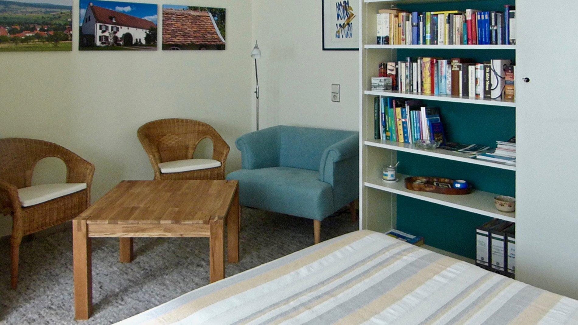 Sitzecke mit drei Sesseln/Stühlen, Tisch und Bücherschrank