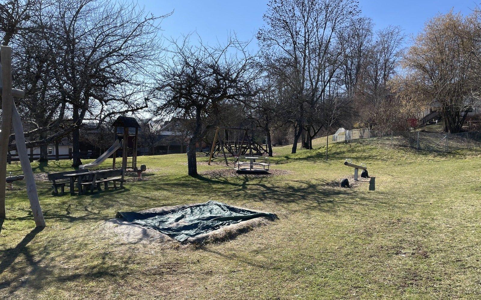 auf einer Rasenfläche ist ein Sandkasten mit einer grünen Folie abgedeckt im Hintergrund sieht man Obstbäume