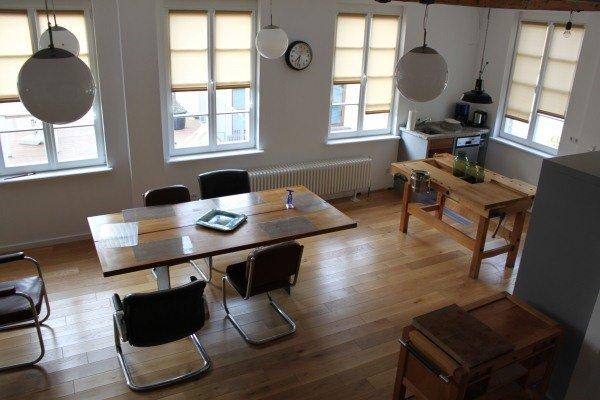 Esstisch mir 5 Stühlen auf Holzboden mit großen Fenstern