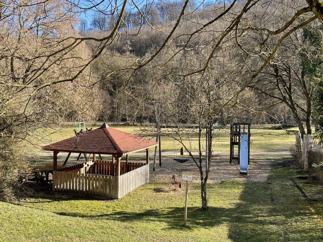 Ein Spielplatz, auf der linken Seite ein Holzunterstand auf der rechten Seite eine blaue Rutsche