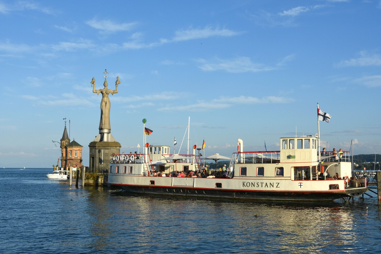 Die historische Fähre im Konstanzer Hafen vor der Imperia mit Blick auf den dunkelblauen Bodensee