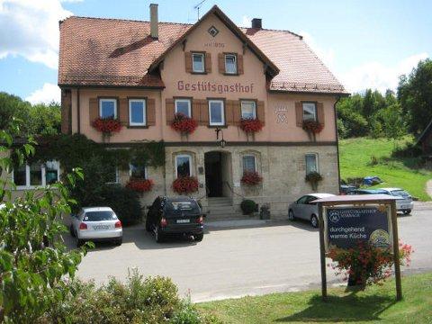 Ein historisches Haus mit orangener Fassade und der Aufschrift Gestütsgasthof.