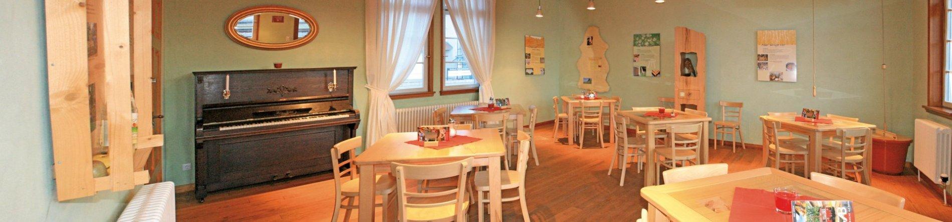 Ein Panorambild eines Raums mit mehreren Tischen und Stühlen und mintgrünen Wänden. An der Wand steht ein Klavier und es hängen mehrere Tafeln. Der Raum ist gemütlich eingerichtet.
