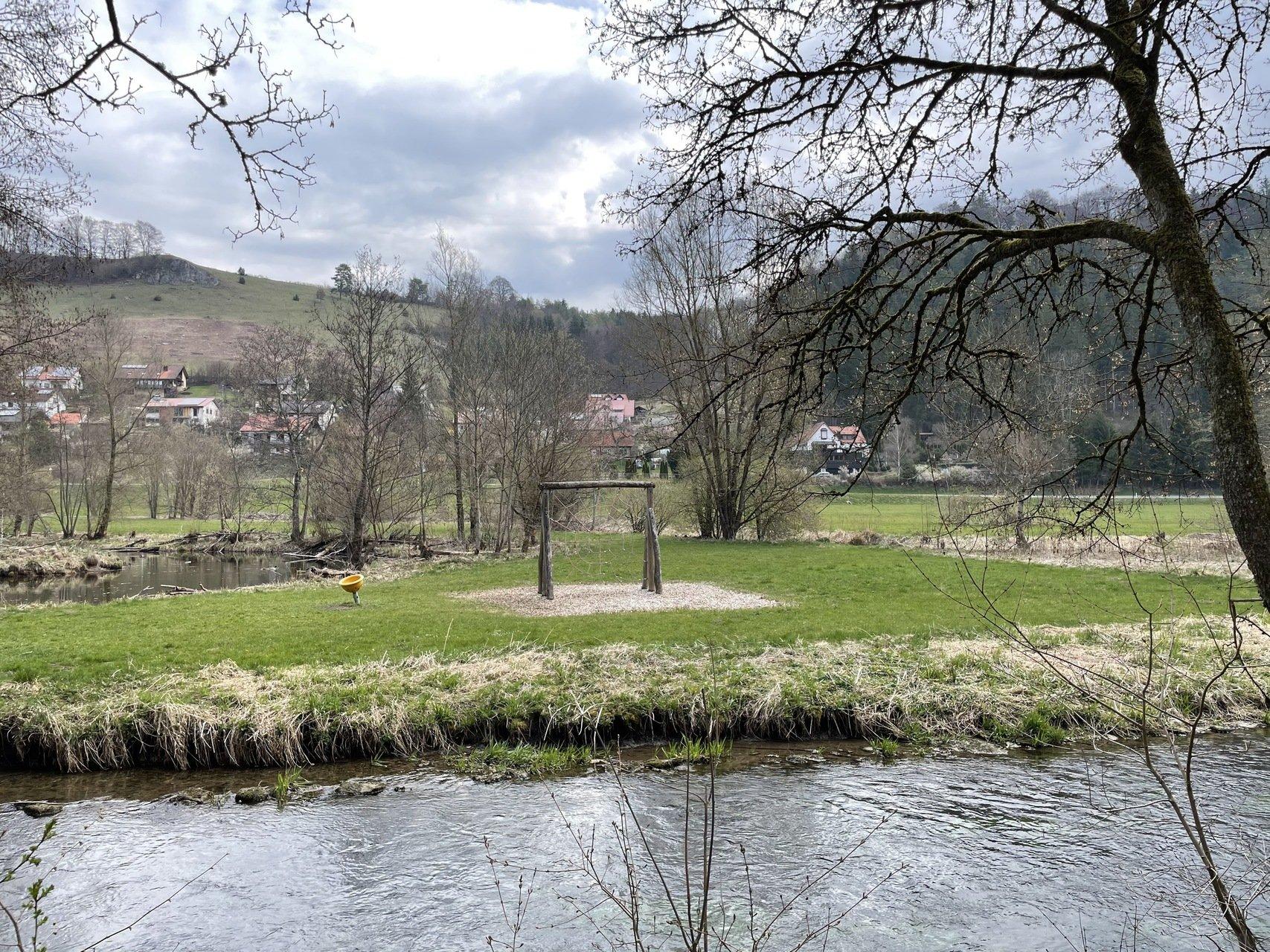 Im Vordergrund fließt ein Fluß in Hindergrund ist ein Kletternetz auf der linken Seite steht eine gelbe Wippe
