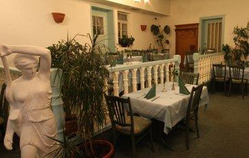 Ein Raum mit einer kleinen abgetrennten Terrasse. Überall stehen gedeckte Tische und Stühle. An den Wänden hängen Pflanzen, vereinzelt stehen Statuen.
