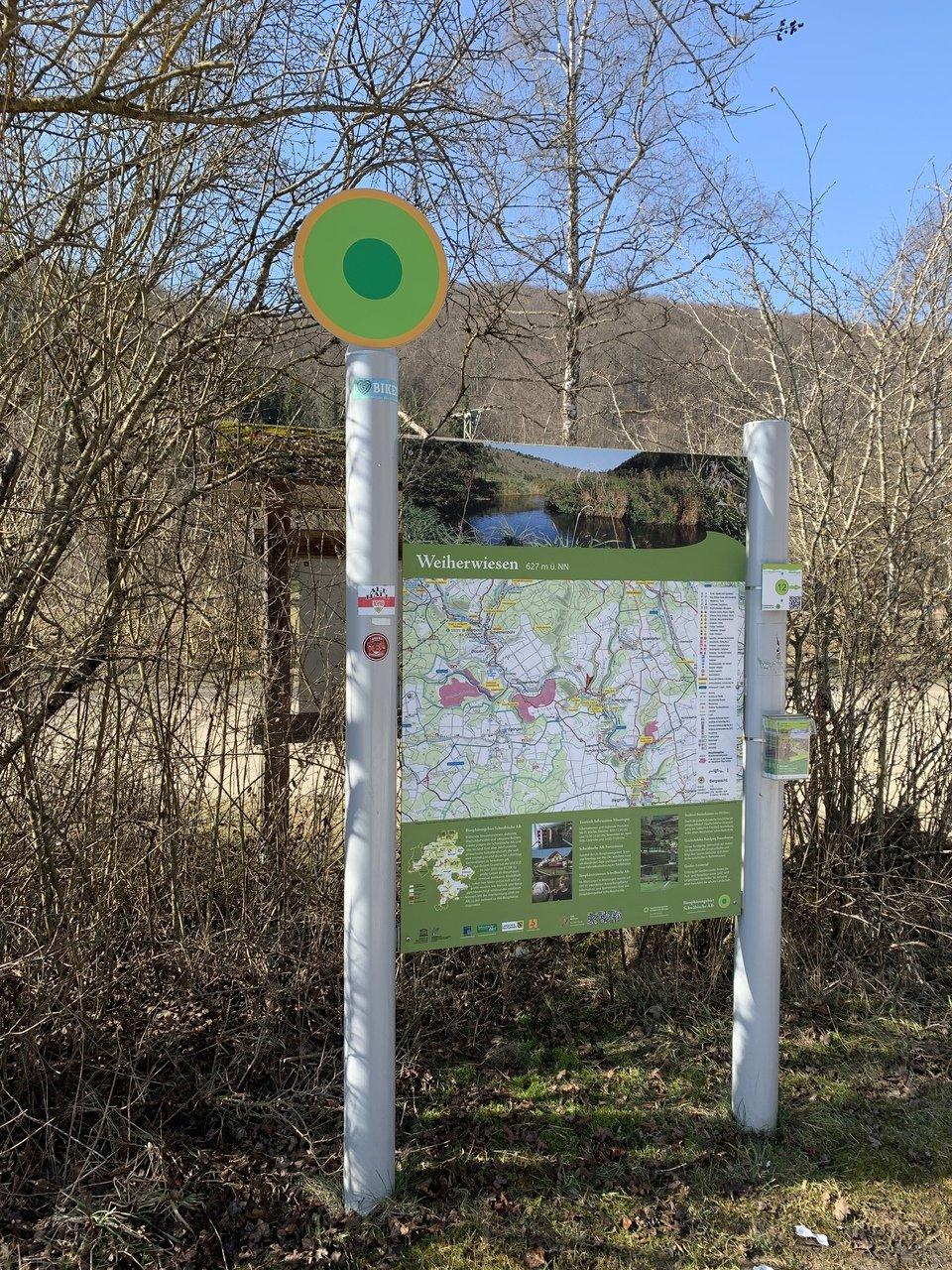 Wanderparkplatzschild mit Prospektbox und Wegweiser.
