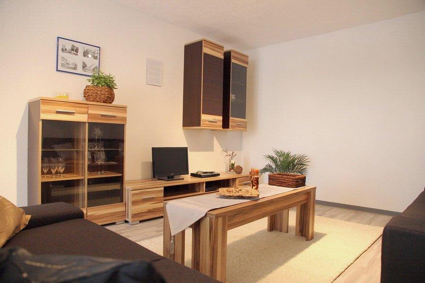 Helles Wohnzimmer mit hellen Holzmöbeln und einer dunkelgrauen Couch