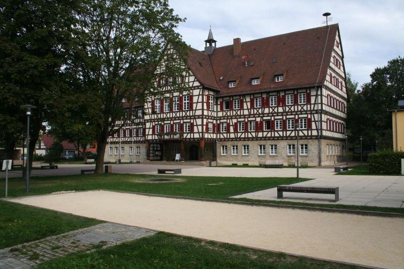 Vor dem Rathaus gibt es mehrere Bänke, eine Boulbahn und ein Trampolin. Hinter der Boulbahn stehen Bäume.
