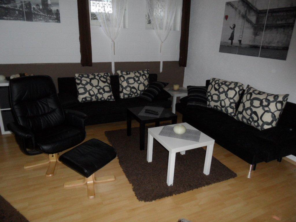 Wohnzimmer mit einer schwarzen Couch und einem Sessel sowie zwei Couchtischen