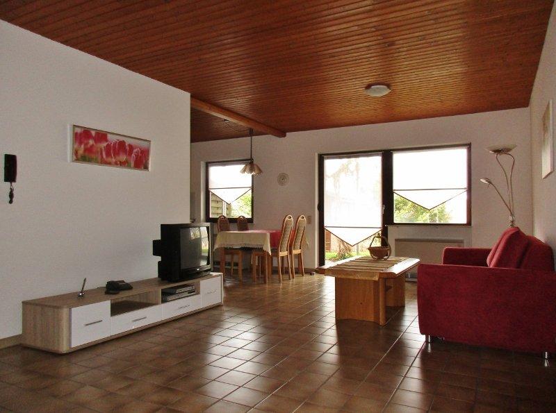 Rote Couch mit Fernseher auf Fliesenboden