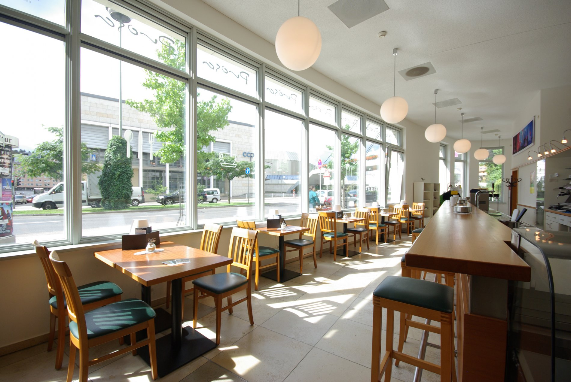 Interior Café Prosa with tables by the window and view to CCP