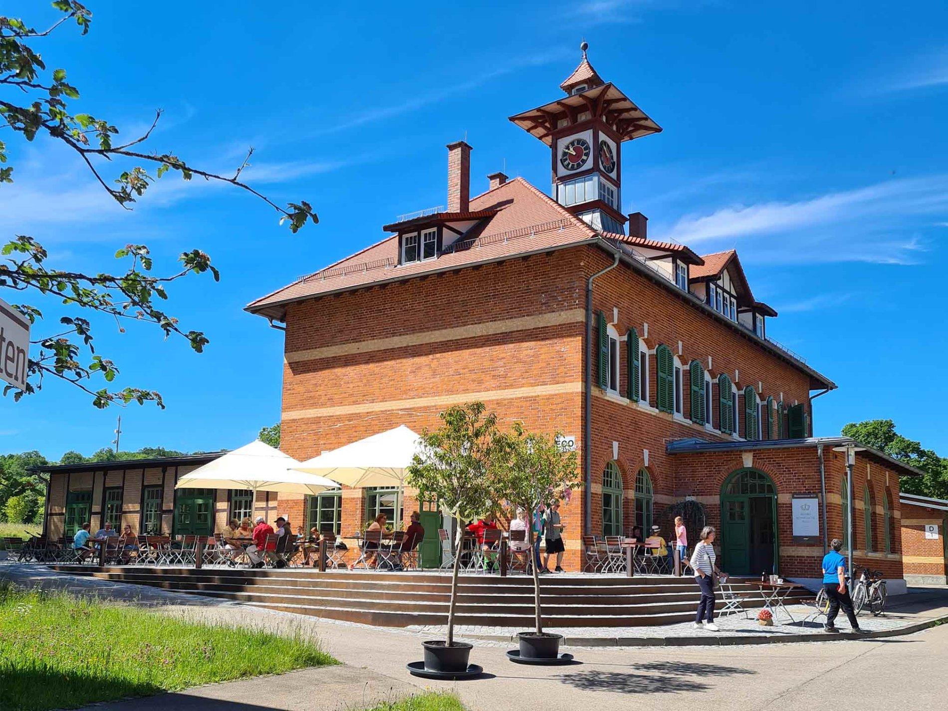 Ein Backsteingebäude mit historischem Turm mit einer Uhr. Davor eine Terasse mit Sitztischen und Sonnenschirmen. Dort sitzen einige Personen, weitere stehen vor dem Gebäude. Es ist sonnig und der Himmel ist blau.