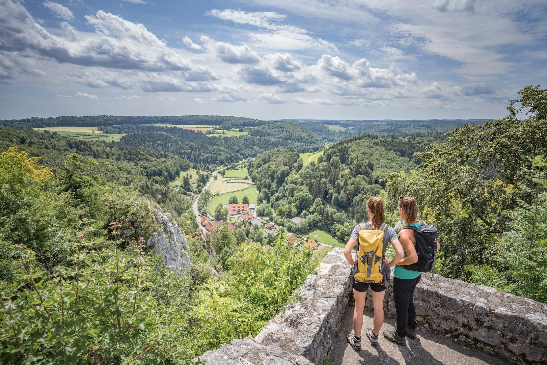 Zwei Wanderer*innen stehen auf einer Burg an einer Ecke einer Plattform. Sie stehen mit dem Rücken zum Fotograf und blicken in die gleiche Richtung ins Tal, durch das sich ein Fluss schlängelt und sich ein kleines Dorf befindet.