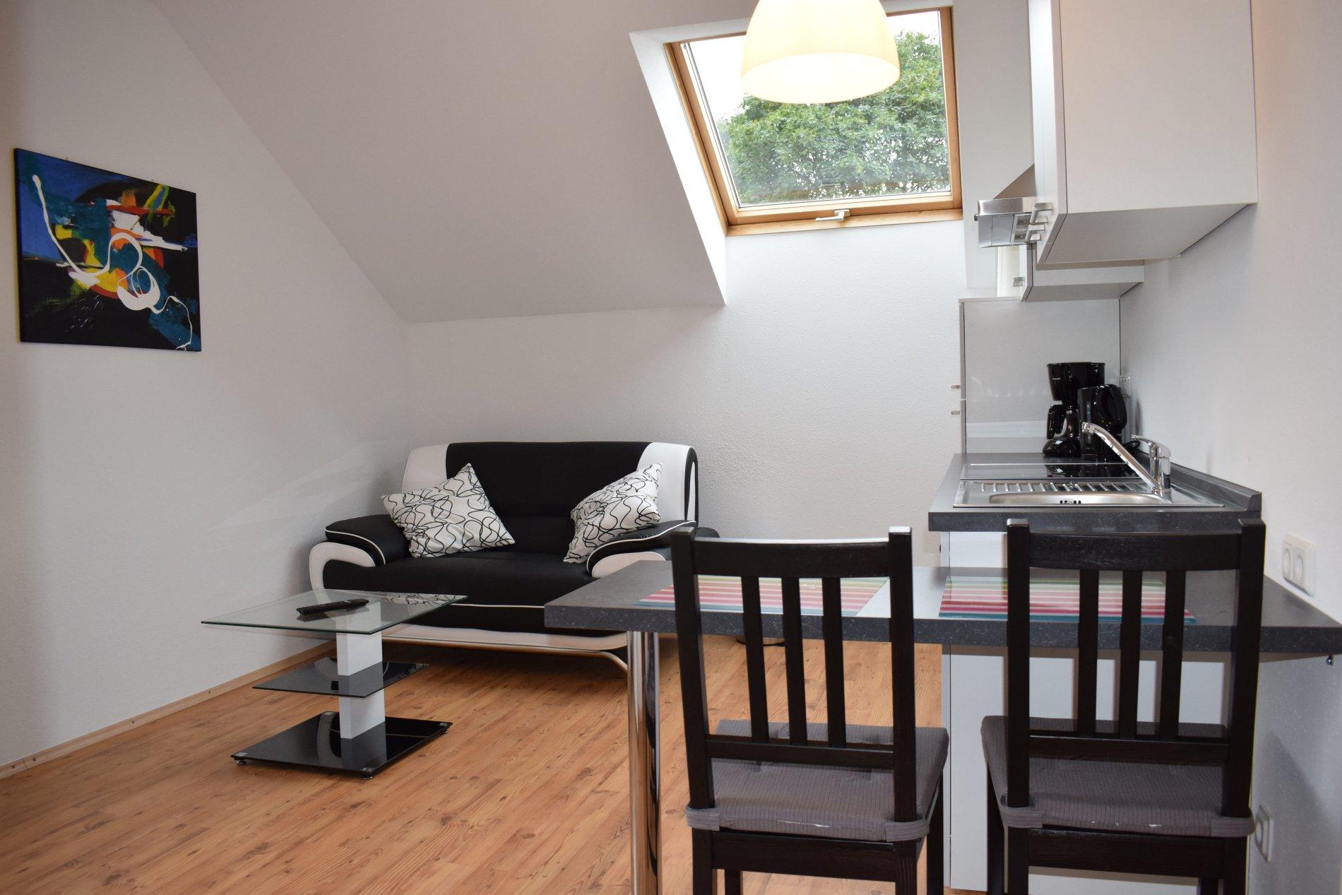 Wohn und Essbereich mit Tisch, zwei Stühlen, Sofa und Couchtisch