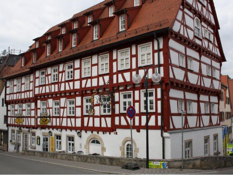 Ein großes Fachwerkgebäude von außen, an dem ein altes Postschild hängt.