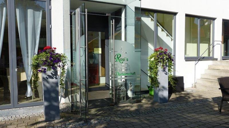 Ein Gebäude von außen mit einer großen Glastür. Neben dem Eingang stehen auf Säulen rote Blumen.