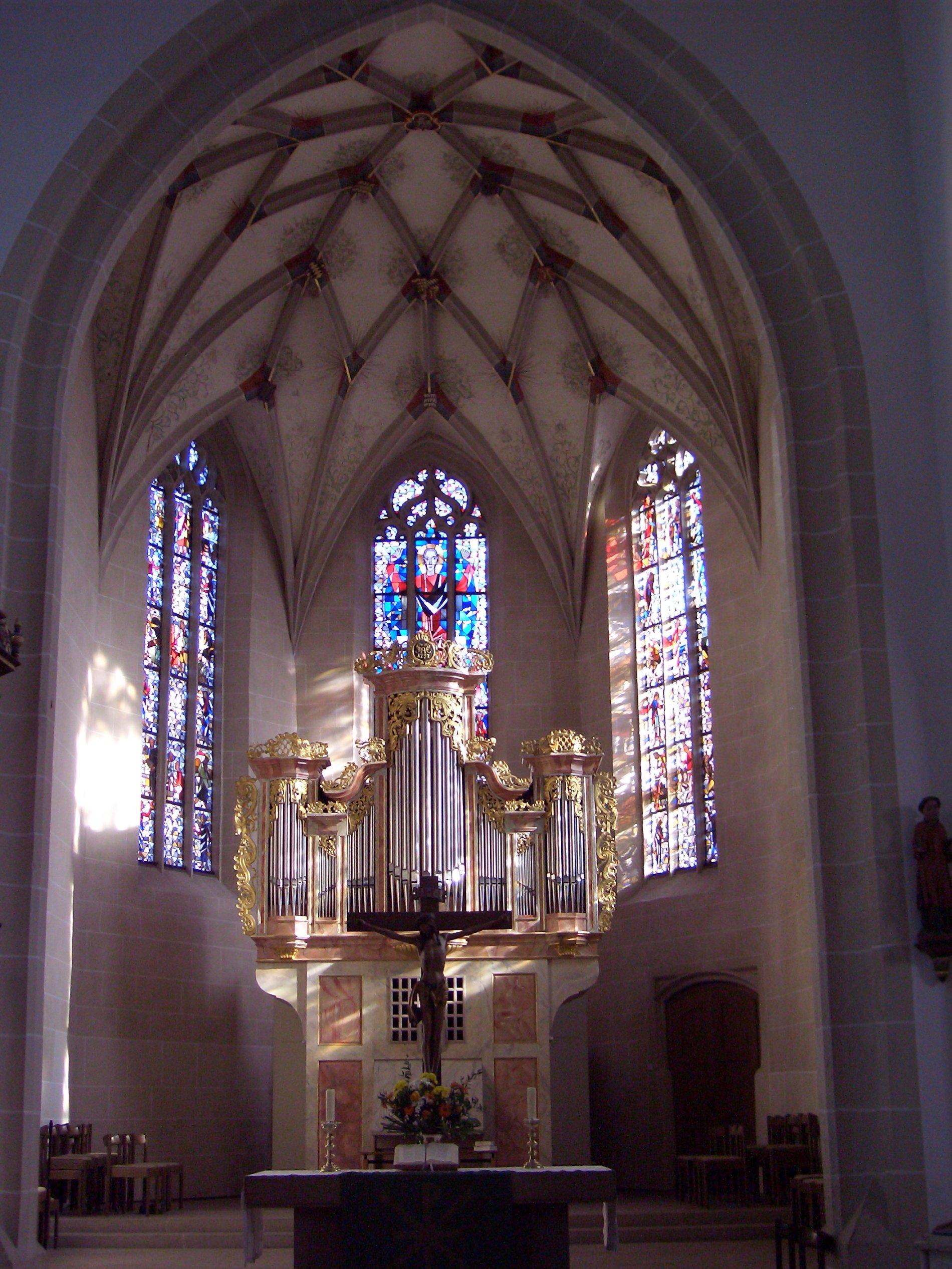 Altar Martinskirche Münsingen, im Hintergrund steht ein Kreuz und die Orgel. 3 Kirchenfenster mit bunten Bildern