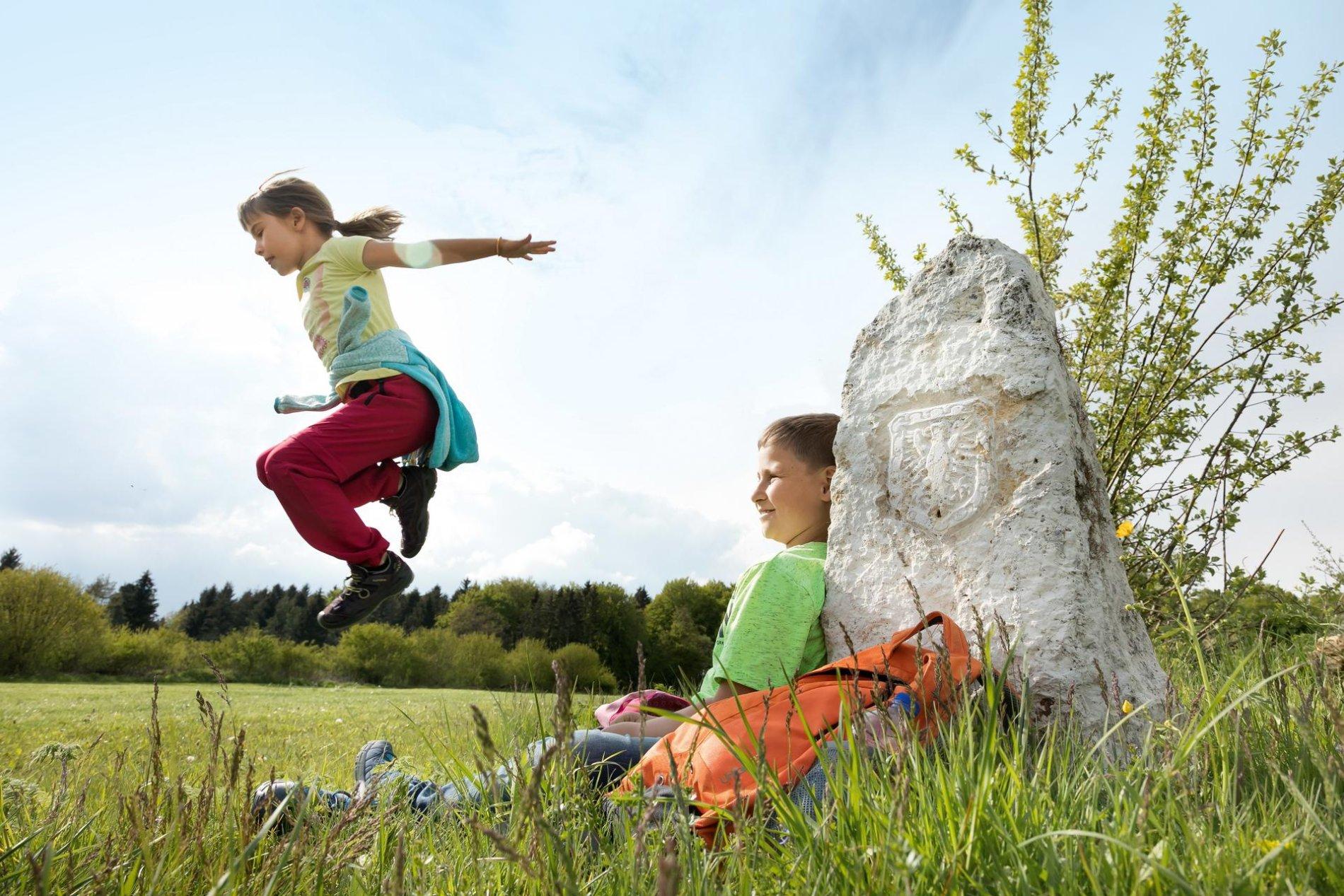 Ein Kind sitzt lächelnd an einem hellen Stein mit einem Wappen darauf und lehnt sich mit dem Rücken dagegen.ein anderes Kind springt hoch über seine Beine. Im Hintergrund ist Wiese und Wald. Der Himmel ist leicht bewölkt.