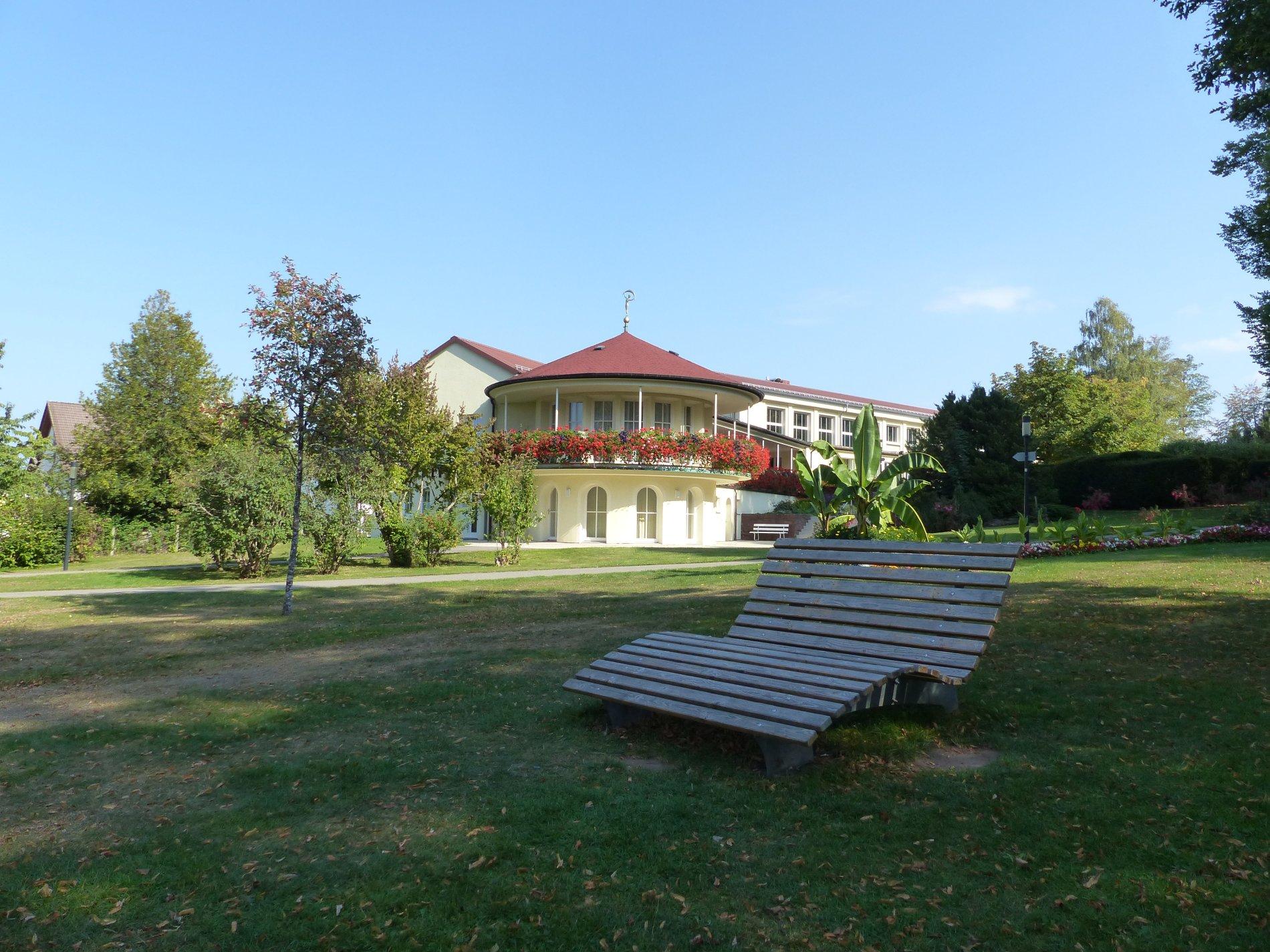 Himmelsliege Wiese Kurpark Schömberg, auf der grünen Wiese mit dem Kurhaus und dem Blumenswing im Hintergrund, Heilklima, Enz-Nagold Platte