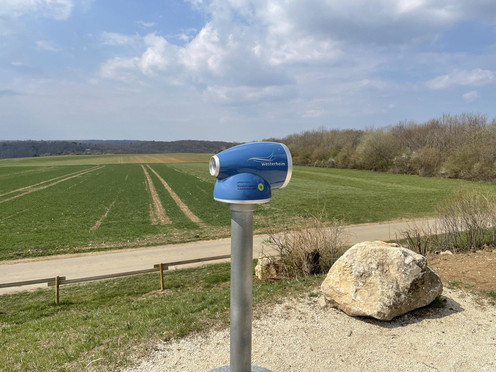 In der Bildmitte ein blaues Erklär-Fernrohr neben einen großen Stein, im Hinderdgrund ein Feld