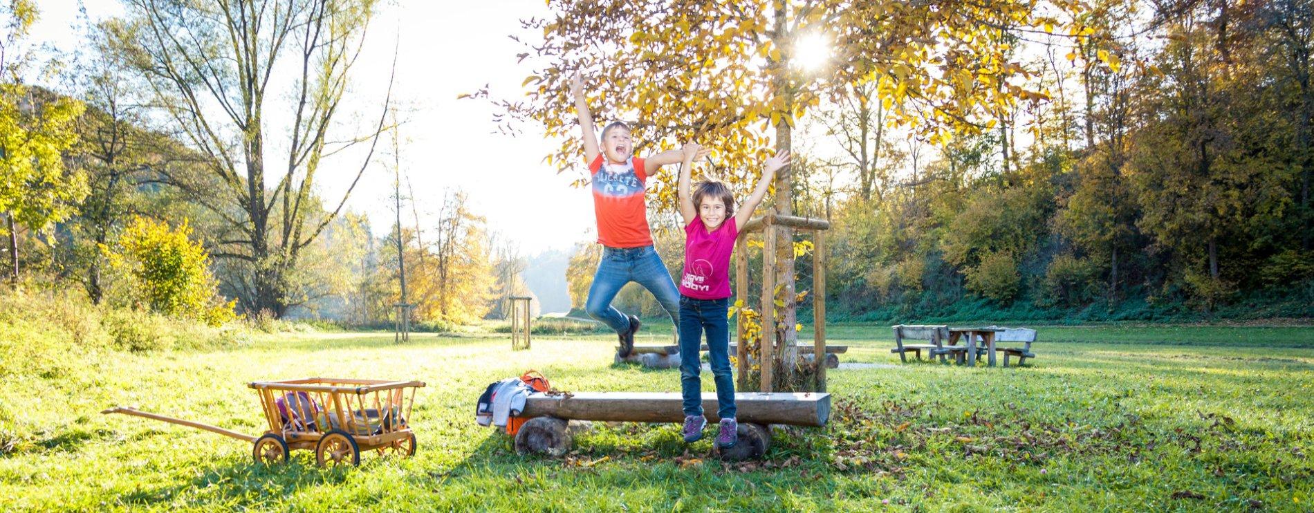 Zwei Kinder springen amüsiert von einer kleinen Holzbank. Dahinter steht ein herbstlicher Baum, durch den die Sonne blitzt. Daneben steht ein Bollerwagen. Im HIntergrund ist eine Grillstelle.