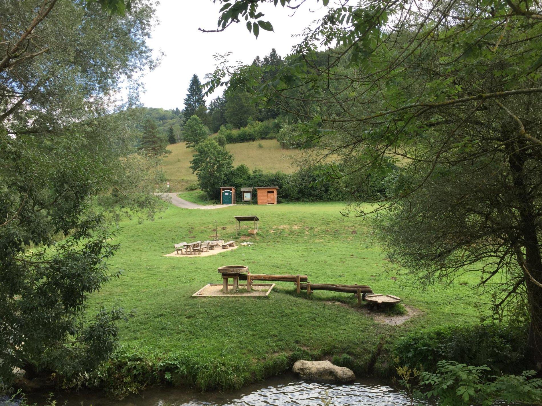 Eine Liegewiese direkt an einem Fluß mit Bäumen, eine Grillstelle und WC Häuschen