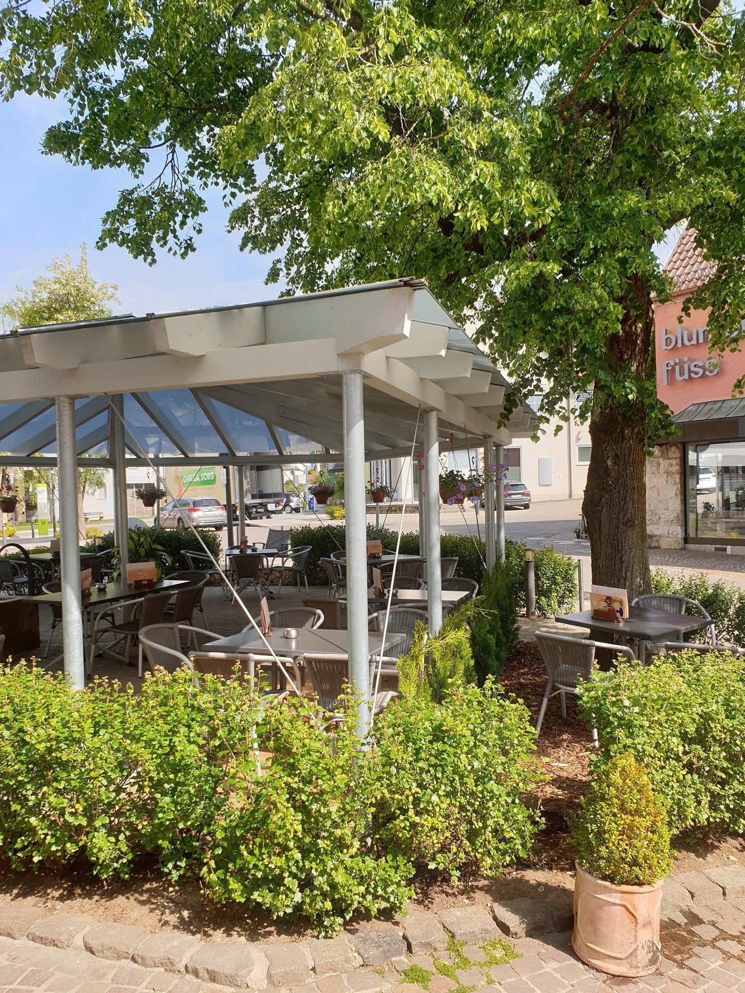 Ein Pavillion unter dem mehrere Tische und Stühle stehen. Drumherum sind viele Pflanzen, Blumen und ein Baum. Es ist sonnig.