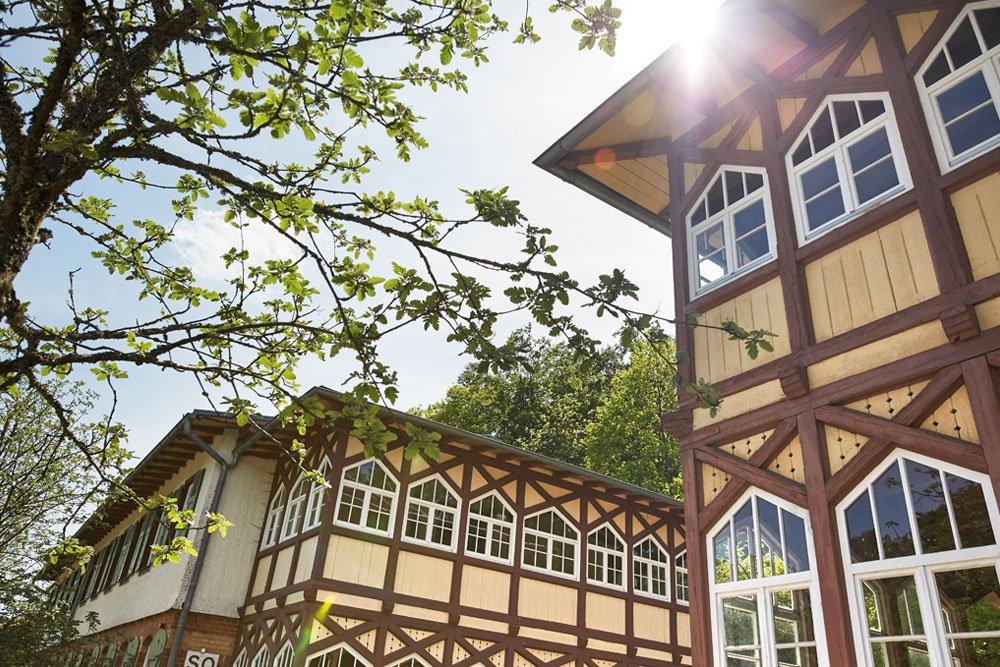 Ein historisches Gebäude mit einer verzierten Holzfassade. Über dem Dach blitzt die Sonne hervor. Dazwischen ein paar Bäume.