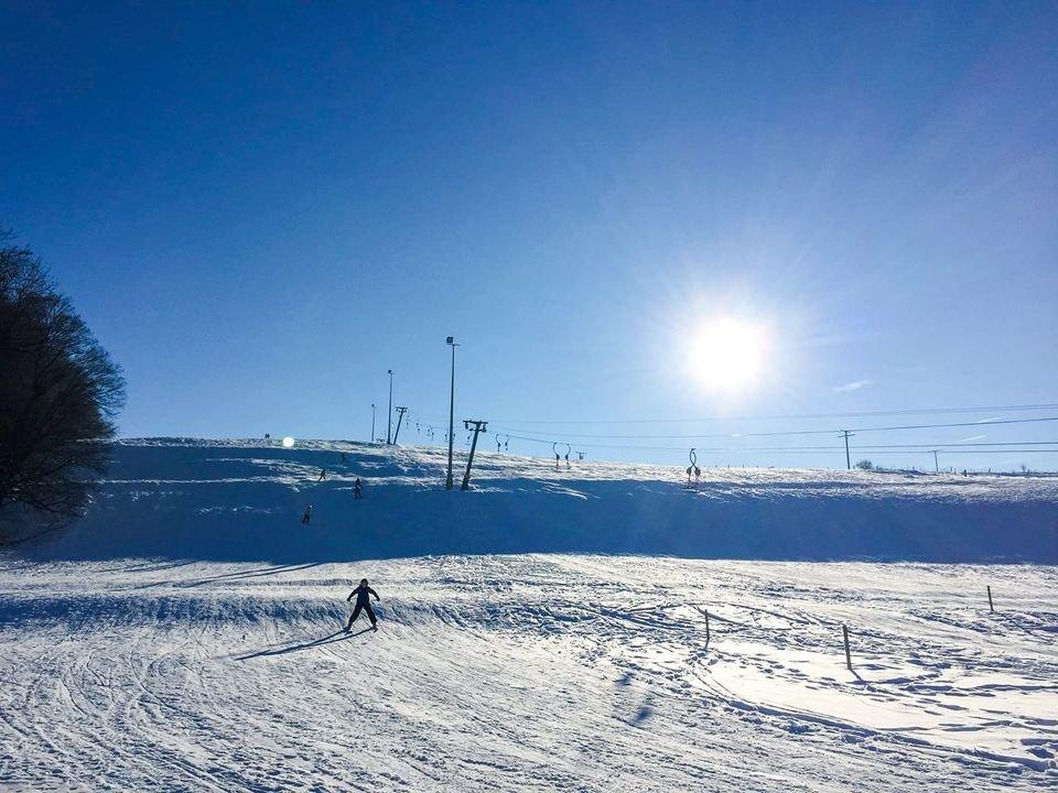 ein schneebedeckter Hang m it vielen bunt angezogenen Menschen die entweder Ski fahren oder rodeln