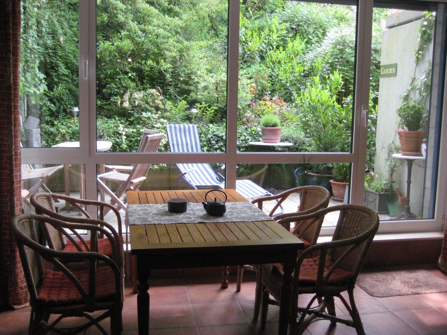 Essbereich mit vier Stühlen und Ausblick auf die grüne Terasse