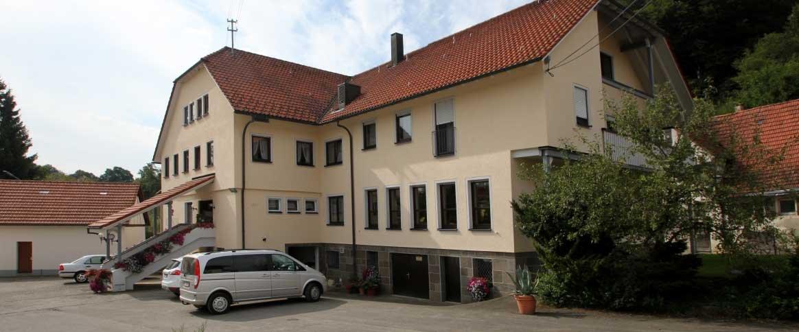 Ein Gebäude von außen mit einem Parkplatz davor.