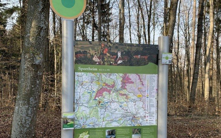 Wanderparkplatzschild mit Prospekthalter und Wegweiser.