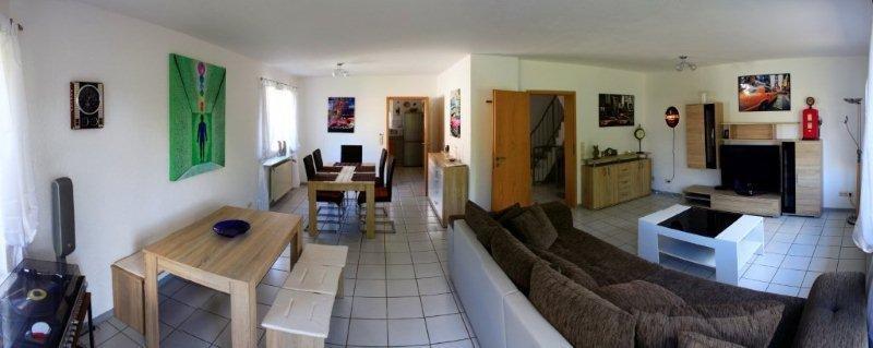 Braune Couch mit Fernseher und zwei Esstische mit Bänken und Stühle, weißer Fliesenboden