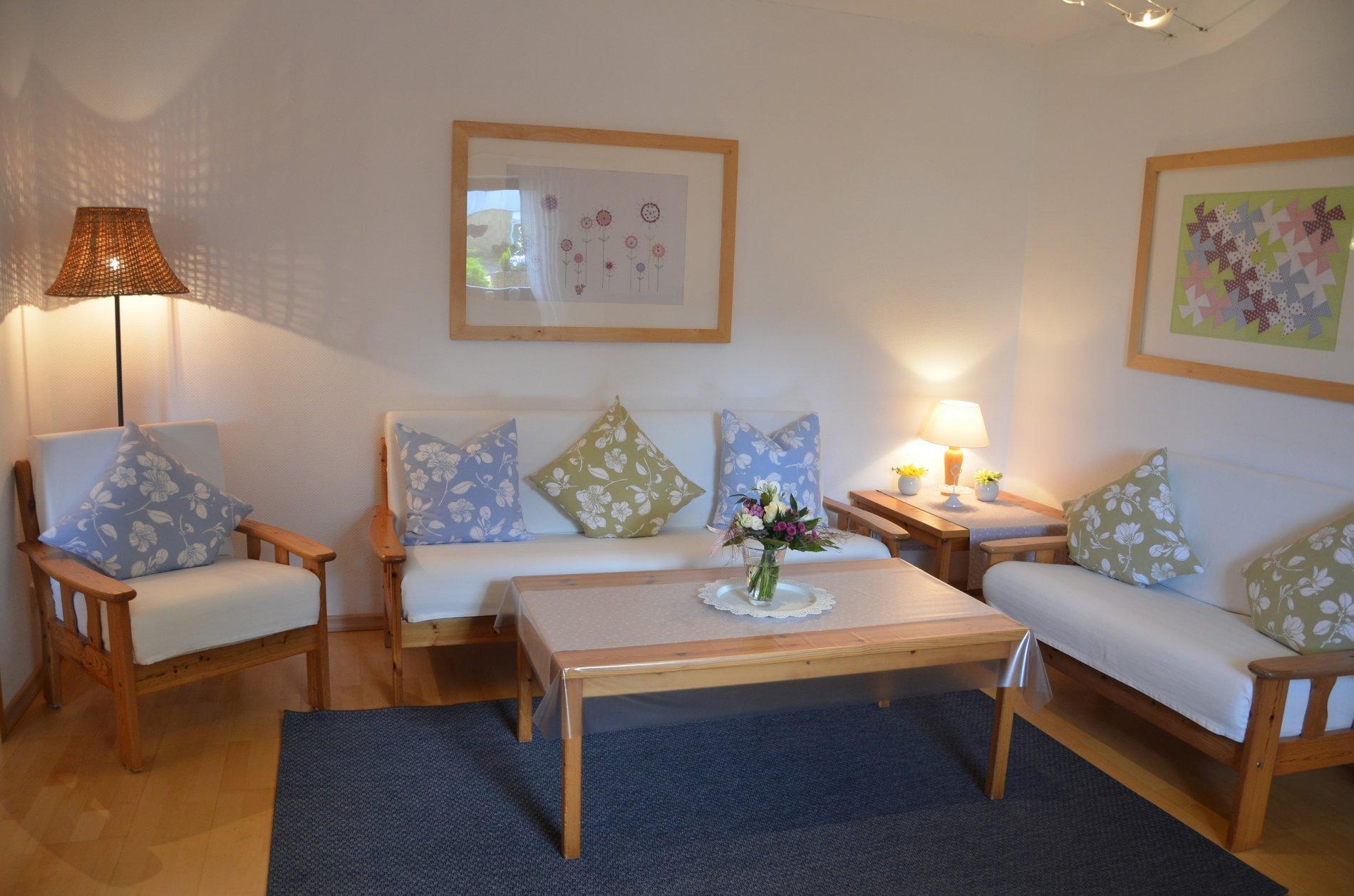 Zwei Sofa mit Sessel in weiß mit Wohnzimmertisch und Teppich auf Laminat