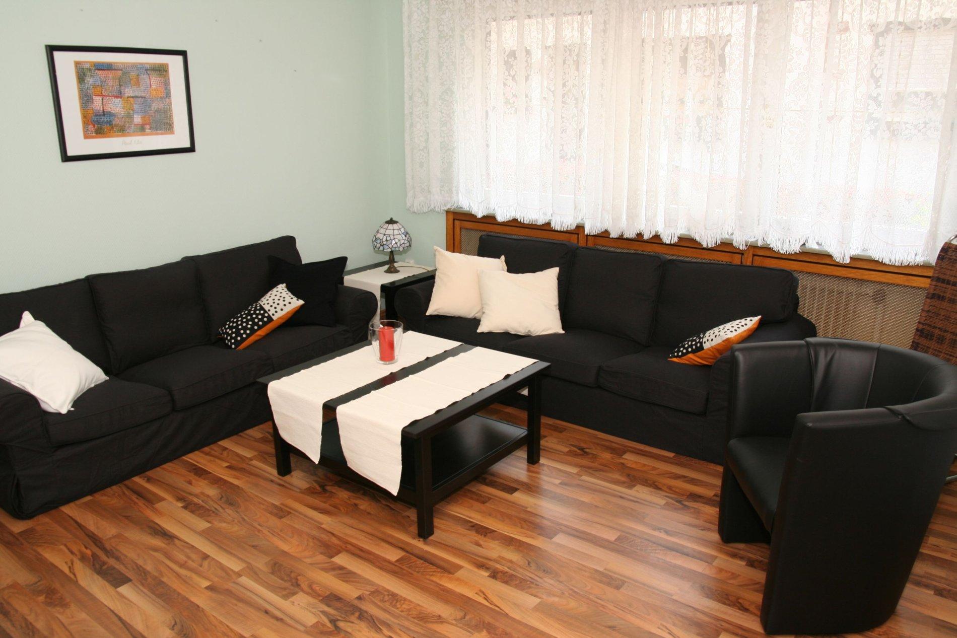 Wohnzimmer mit einem schwarzen Sofa und einem Sessel auf braunem Laminat