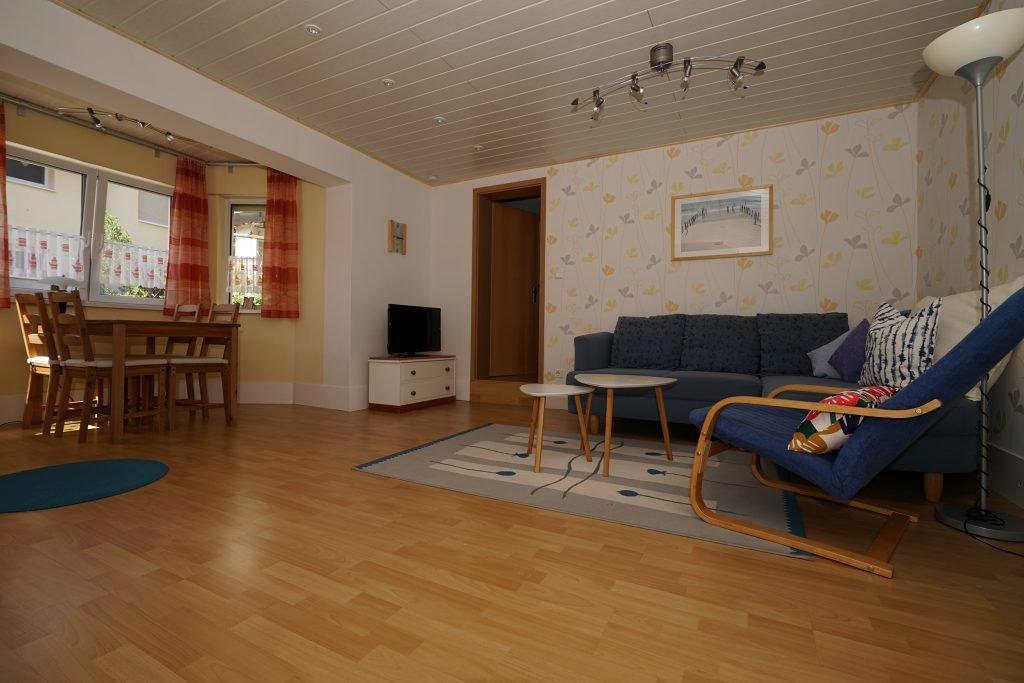 Geräumiges Wohnzimmer mit blauer Couch und Sitzecke