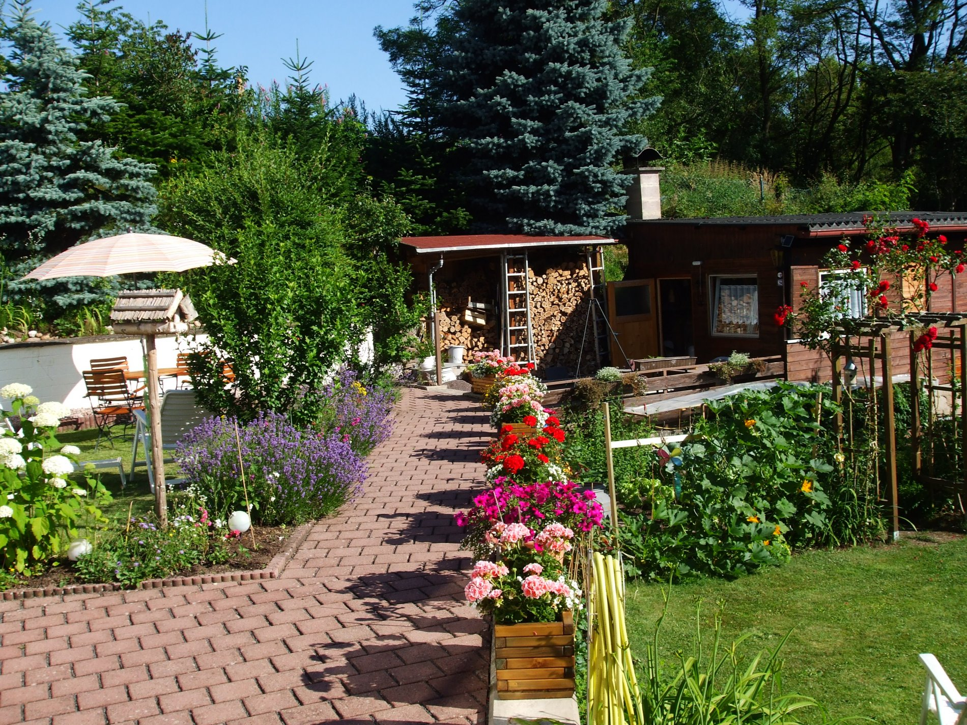 Garten mit Gartenhaus, Tisch mit drei Stühlen und Blumen