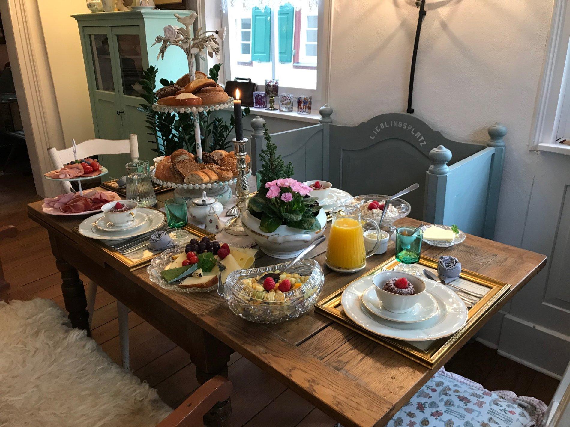 Im Raum steht ein gedeckter Tisch mit Tellern und Tassen, Essen und Tinken. Um den Tisch steht eine Bank und 3 Stühle, das Licht brennt.